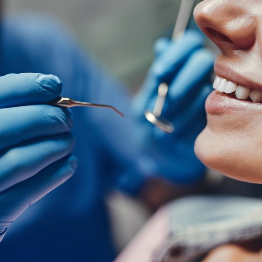 Attractive young woman in stomatology clinic with male dentist. Healthy teeth concept.